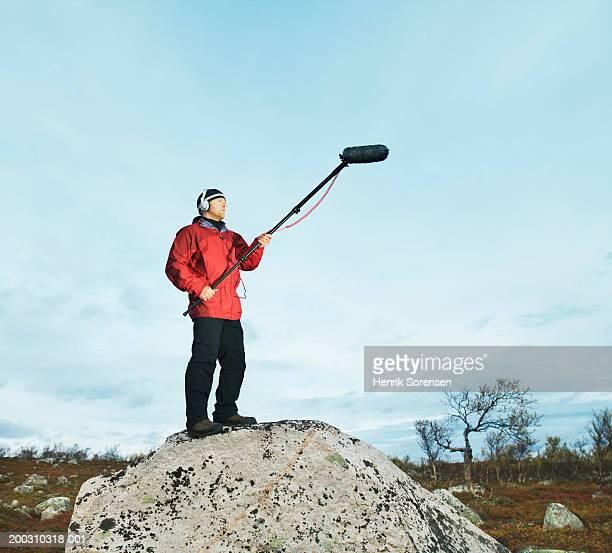 man on rock holding boom microphone, wearing headphones - girafe photos et images de collection