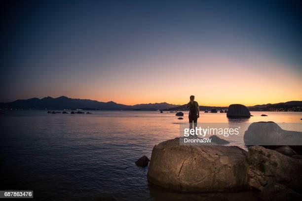 Man on rocks contemplating  sea.