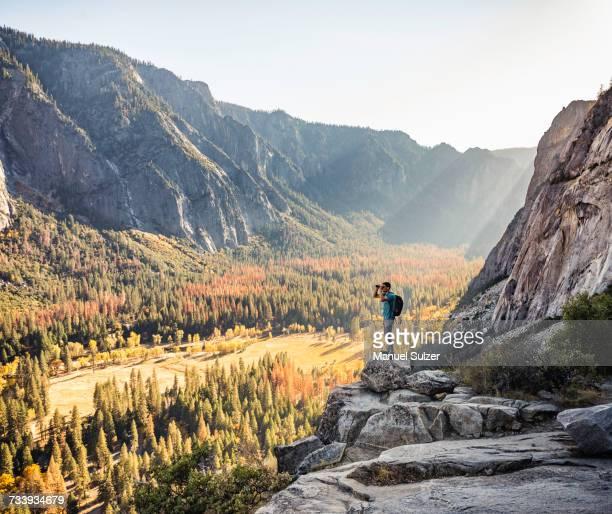 Man on rocky edge looking out through binoculars, Yosemite National Park, California, USA