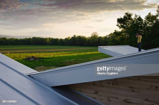 Man on roof admiring view of rural field