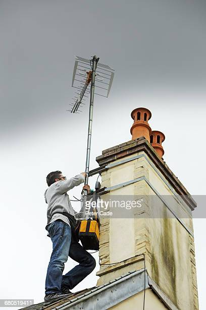 Man on roof fixing arial to chimney