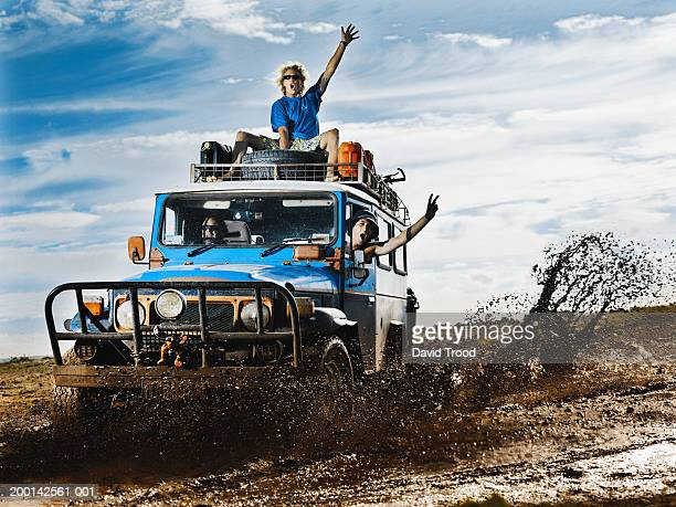 man on roof of 4x4, two men inside, shouting, arms raised - 4x4 stock pictures, royalty-free photos & images