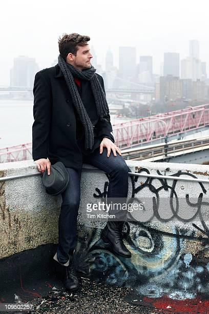 Man on rooftop, sitting on ledge