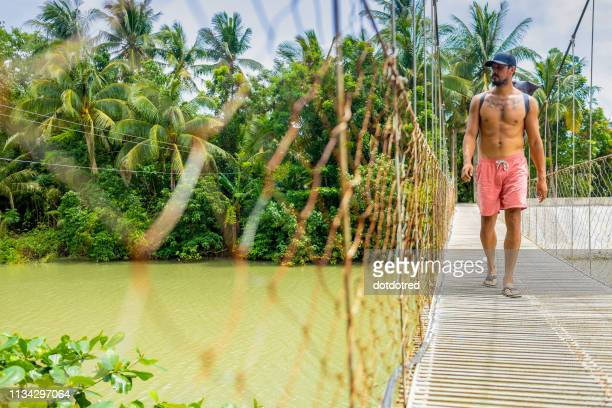 man on rope bridge, pagudpud, ilocos norte, philippines - zwembroek stockfoto's en -beelden