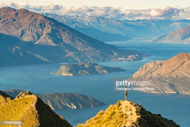 man on roys peak lookout, new zealand. - lago wanaka - fotografias e filmes do acervo