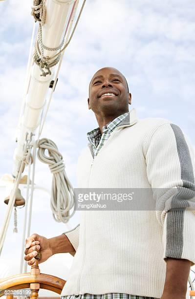 Un homme sur un voilier tenant la roue