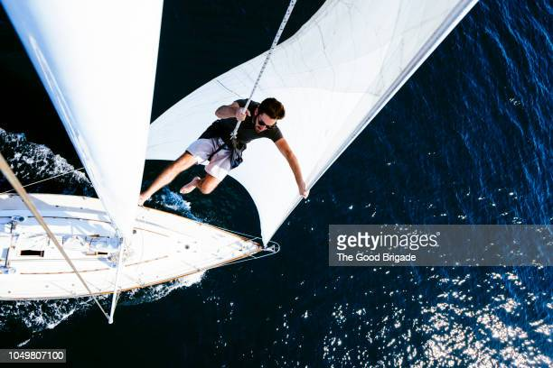 man on sailboat wearing safety harness - segeln stock-fotos und bilder