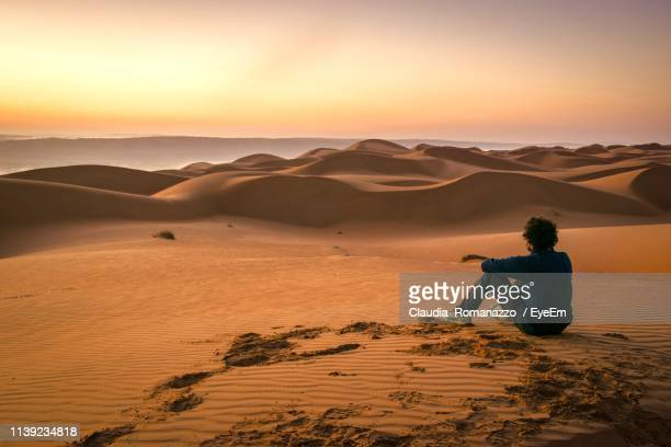 man on sand dune in desert against sky during sunset - claudia romanazzo foto e immagini stock