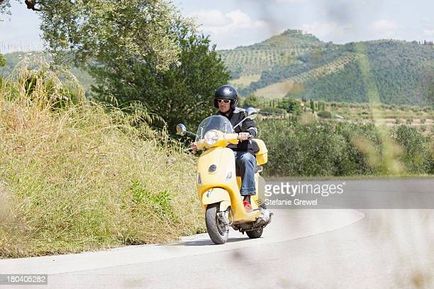 man on scooter riding around corner - moped stock photos and pictures