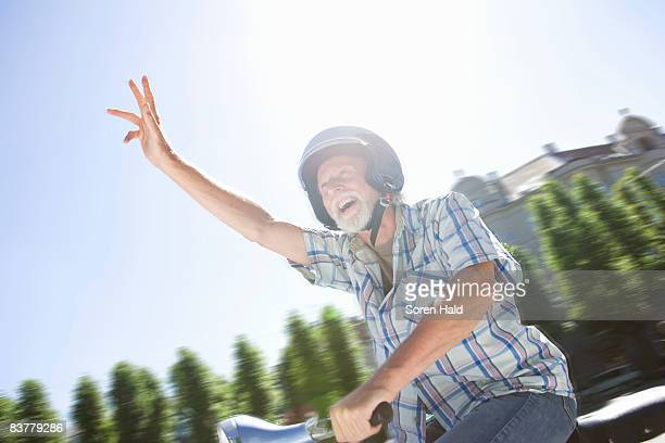 Man on scooter, waving