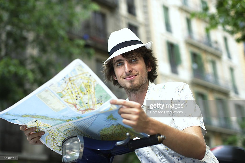 Man on scooter with map outdoors : Stock Photo