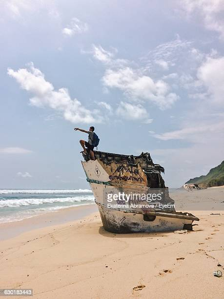 Man On Shipwreck At Beach Against Sky