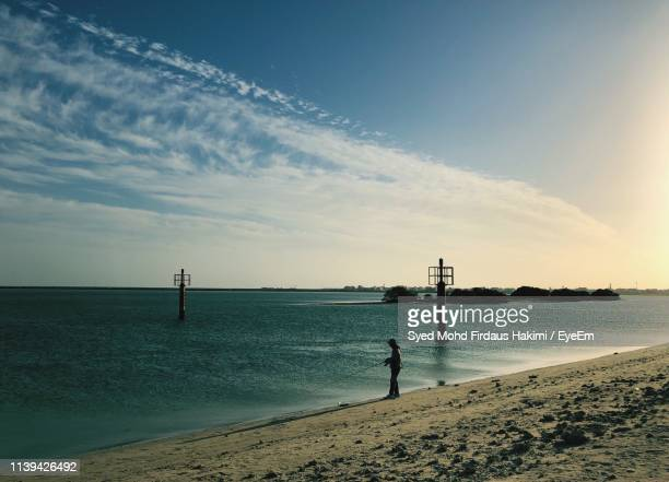 man on shore at beach - hakimi stock photos and pictures