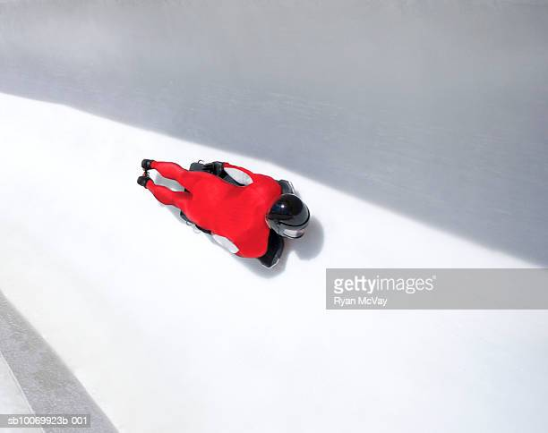 Man on skeleton sled down ice track, high angle view