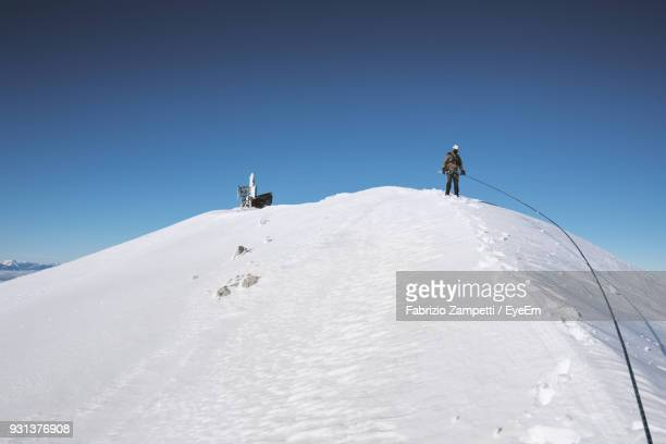 man on snow covered mountain against clear sky - fabrizio zampetti foto e immagini stock