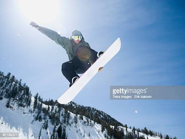 man on snowboard in air, wasatch mountains, utah, united states - boarding stock pictures, royalty-free photos & images