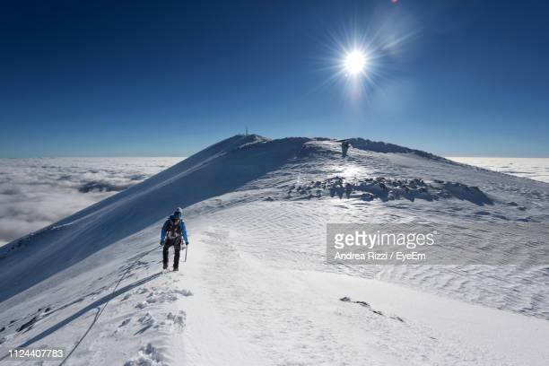 man on snowcapped mountain against blue sky - andrea rizzi stockfoto's en -beelden
