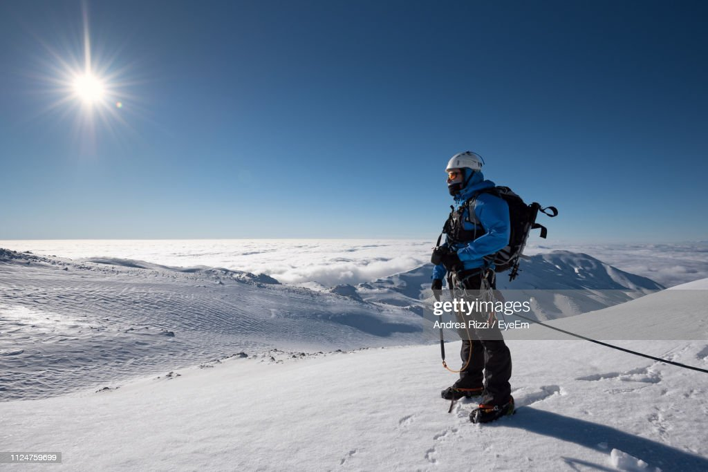 Man On Snowcapped Mountain Against Blue Sky : Foto stock