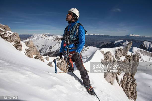 man on snowcapped mountain against sky - andrea rizzi fotografías e imágenes de stock
