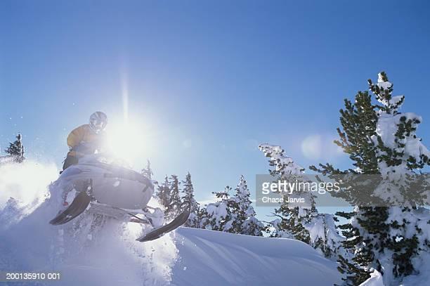 man on snowmobile (lens flare) - snowmobiling - fotografias e filmes do acervo
