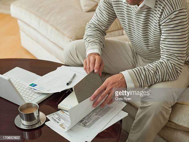 Homme sur le canapé, examiner des documents