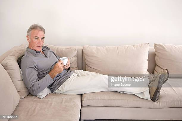 man on sofa holding teacup - gray pants stock pictures, royalty-free photos & images