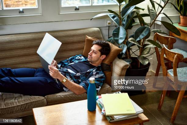 man on sofa using laptop in comfortable office - one mid adult man only stock pictures, royalty-free photos & images