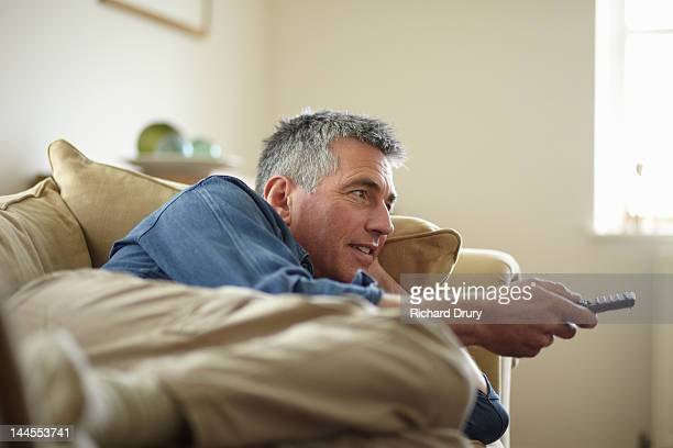 Man on sofa using tv remote control