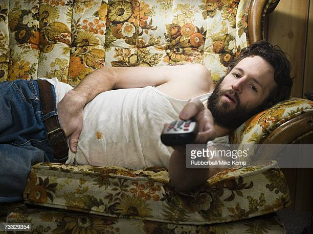 man on sofa with television remote - hillbilly stock pictures, royalty-free photos & images