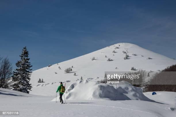 Mann auf Split Snowboard Wandern in verschneite Landschaft