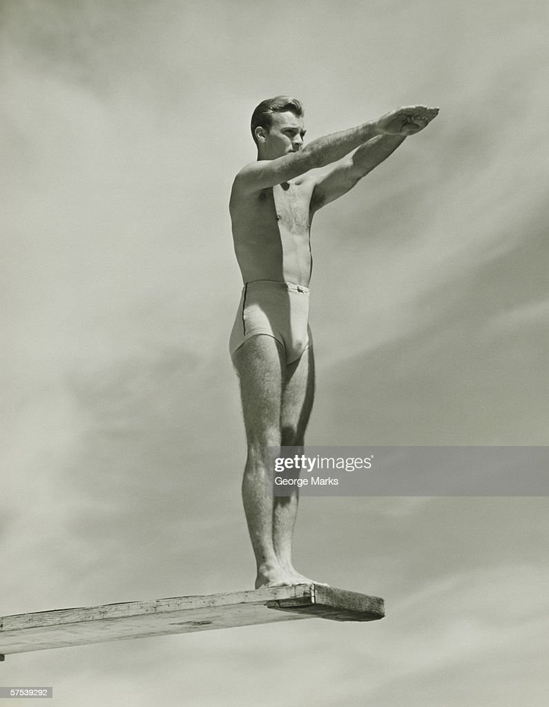 Man on springboard ready to jump, (B&W), low angle view : Stock Photo