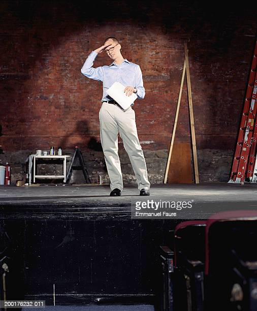 man on stage in theater with hand on forehead - audition stock pictures, royalty-free photos & images
