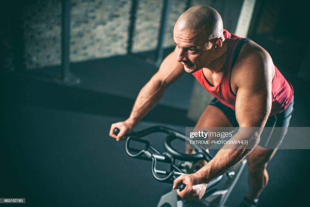 Man op stationaire fiets : Stockfoto