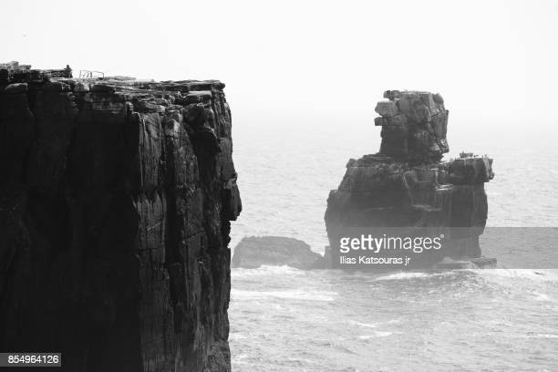 Man on steep cliff with Nau dos Corvos rock in the sea