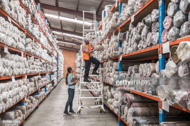 Man on stepladder with female colleague in carpet warehouse