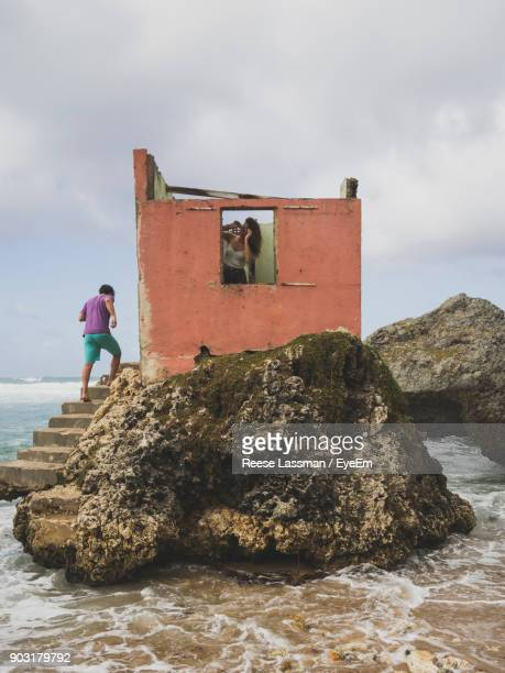 Man On Steps Of Abandoned Built Structure At Beach Against Sky
