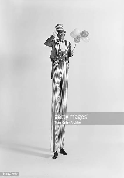 Mann auf Stelzen holding Ballons, Lächeln, Porträt