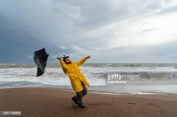 mens op stormachtig strand - wind stockfoto's en -beelden
