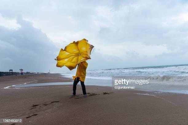 mann am stürmischen strand - bemühung stock-fotos und bilder