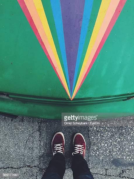 Man on street by car with rainbow painted on hood