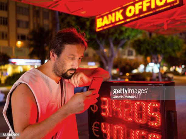 Man on street checking currency with his phone doing electronic banking