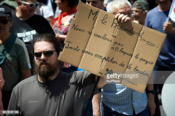 A man on strike shows a piece of cardboard reading 'Mr President we don't want to 'block the country' Just block you to give it away' A quotmaree...