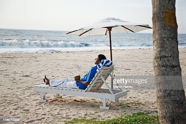 Man (34 years old) on sun lounger looking at sea, Marari beach Alappuzha, Kerala, India