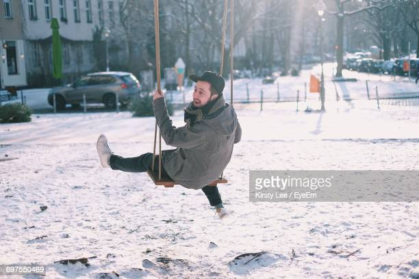 Man On Swing On Snow Covered Playground
