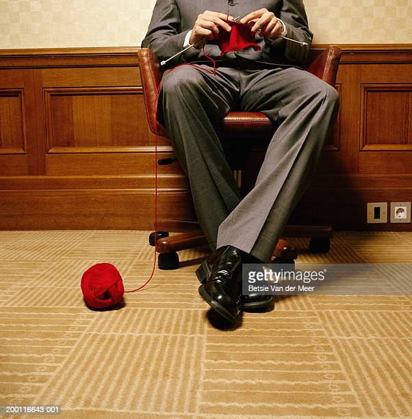 Man on swivel chair knitting, ball of wool at feet, low section