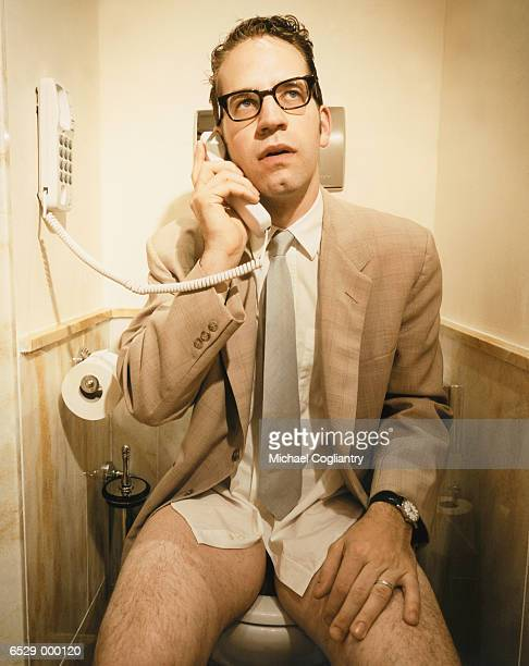 man on telephone in bathroom - número de personas fotografías e imágenes de stock