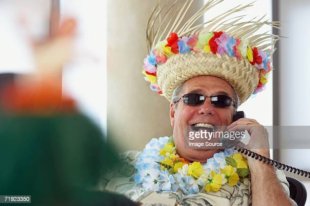 man on telephone wearing holiday clothes - hawaiian shirt stock photos and pictures