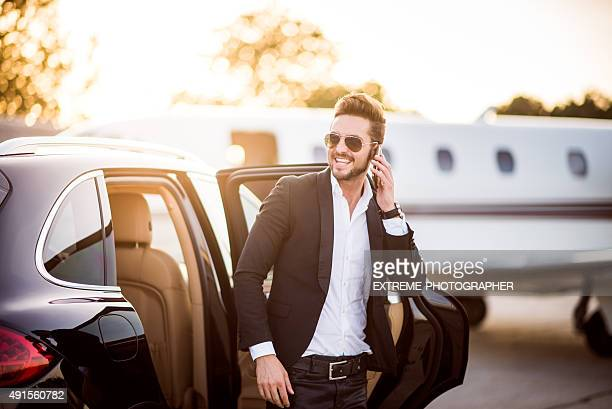man on the airport with phone in his hand - wealth stock pictures, royalty-free photos & images