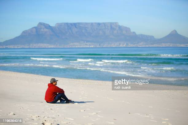 man on the beach in table mountain, cape town - table mountain stock pictures, royalty-free photos & images