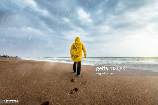 man on the beach on a rainy day - raincoat stock pictures, royalty-free photos & images